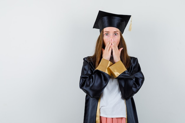 Portret kobiety absolwent, trzymając się za ręce na ustach w ubranie, mundur i patrząc zszokowany widok z przodu