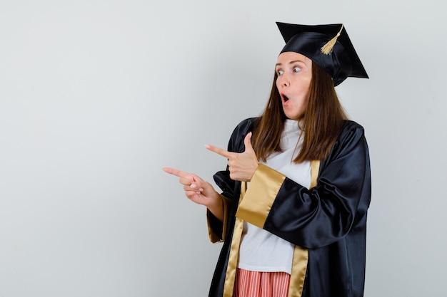Portret kobiety absolwent, wskazując na bok w ubranie, mundur i patrząc zdumiony widok z przodu