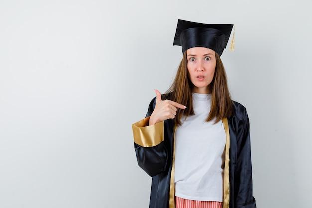 Portret kobiety absolwent, wskazując na siebie w ubranie, mundur i patrząc zdziwiony widok z przodu