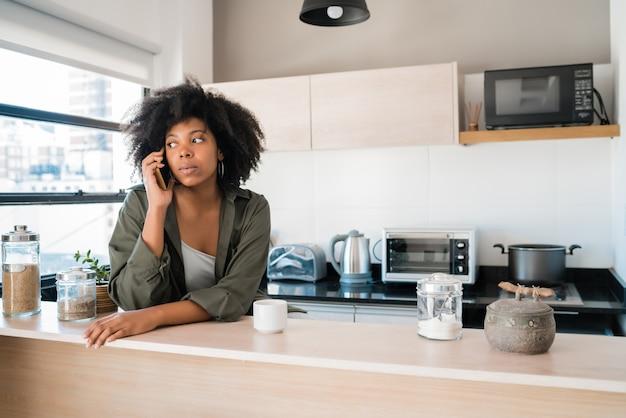 Portret kobiety afro rozmawia przez telefon przy filiżance kawy w domu