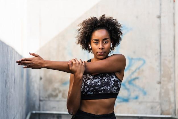 Portret kobiety afro sportowiec, rozciąganie ramion przed ćwiczeniami na świeżym powietrzu