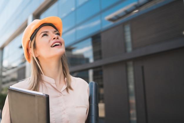Portret kobiety architekta zawodowych w żółtym kasku i patrząc na nowoczesny budynek na zewnątrz. koncepcja inżyniera i architekta.