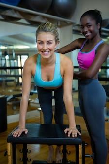 Portret kobiety asystującej trener z krzesłem wunda w studio fitness