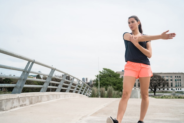 Portret kobiety atletycznej, rozciągając ramiona przed ćwiczeniami na świeżym powietrzu. sport i zdrowy tryb życia.
