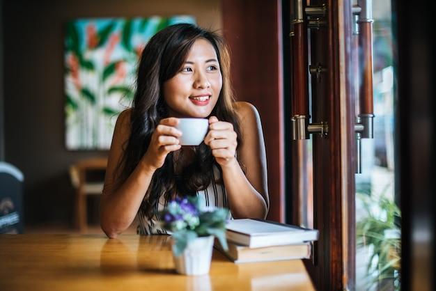 Portret kobiety azjatykci ono uśmiecha się relaksuje w sklep z kawą kawiarni