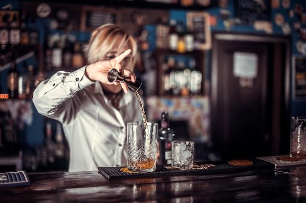Portret kobiety barmanka kończącego drinka przy barze