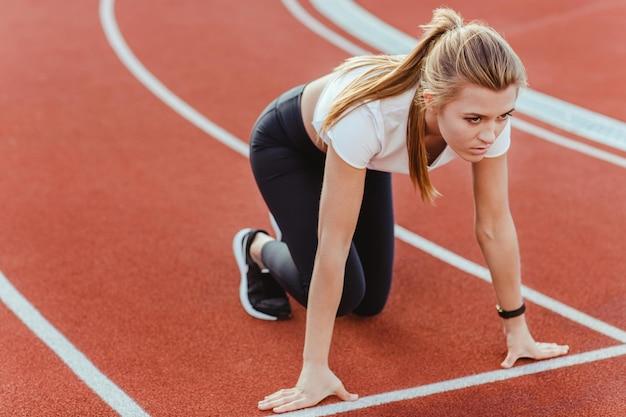 Portret kobiety biegacz stojących w pozycji startowej na stadionie