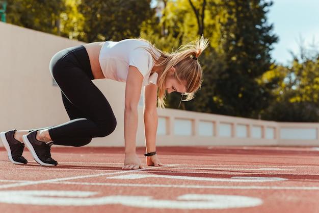 Portret kobiety biegacz w pozycji początkowej na stadionie