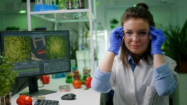 Portret kobiety biolog wprowadzenie okularów medycznych, patrząc w kamerę, siedząc przy stole w laboratorium farmaceutycznym. specjaliści badający mutacje genetyczne opracowujący test dna
