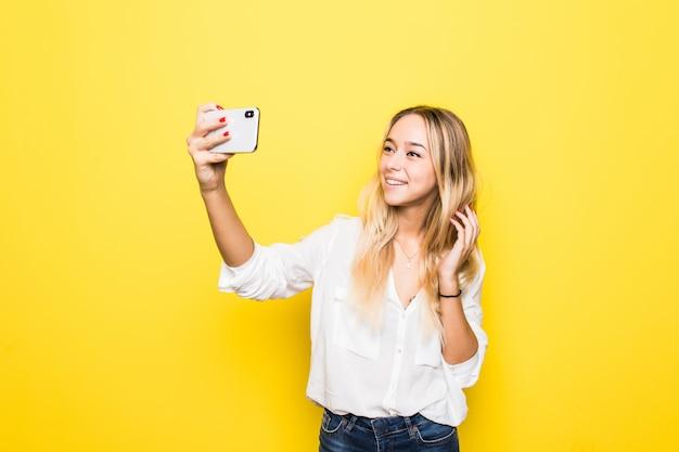 Portret kobiety biorą selfie, trzymając w ręku inteligentny telefon, fotografowanie selfie na białym tle na żółtej ścianie
