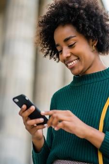 Portret kobiety biznesu afro korzystającej z telefonu komórkowego, stojąc na zewnątrz na ulicy