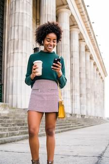 Portret kobiety biznesu afro przy użyciu swojego telefonu komórkowego i trzymając filiżankę kawy podczas spaceru na ulicy na ulicy