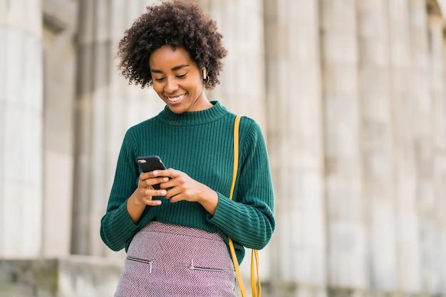 Portret kobiety biznesu afro przy użyciu swojego telefonu komórkowego, stojąc na zewnątrz na ulicy. koncepcja biznesowa i miejska.