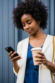 Portret kobiety biznesu afro przy użyciu swojego telefonu komórkowego, stojąc na zewnątrz na ulicy