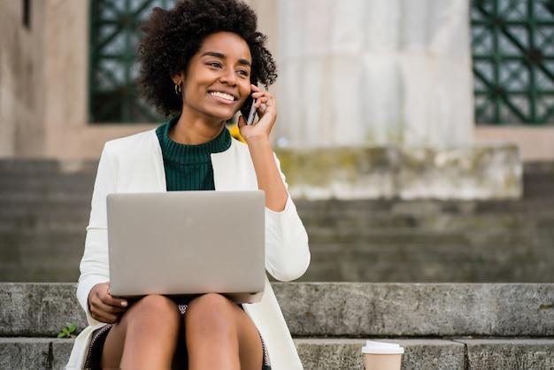 Portret kobiety biznesu afro rozmawia przez telefon i przy użyciu swojego laptopa, siedząc na schodach na zewnątrz