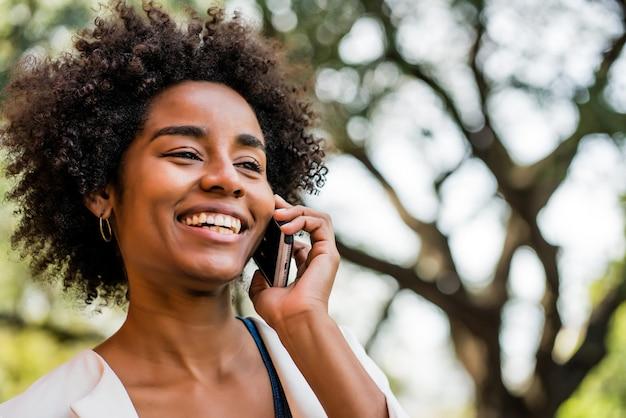 Portret kobiety biznesu afro rozmawia przez telefon stojąc na zewnątrz w parku. pomysł na biznes