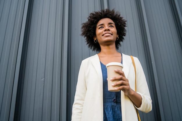 Portret kobiety biznesu afro trzymając filiżankę kawy, stojąc na zewnątrz na ulicy