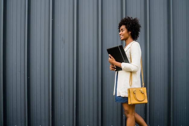 Portret kobiety biznesu afro trzymając schowek podczas spaceru na ulicy na ulicy