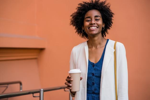 Portret kobiety biznesu afro uśmiechając się i trzymając filiżankę kawy, stojąc na zewnątrz na ulicy