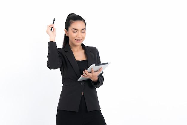Portret kobiety biznesu korzystającej z urządzenia cyfrowego tabletu w czarnym garniturze na białej powierzchni