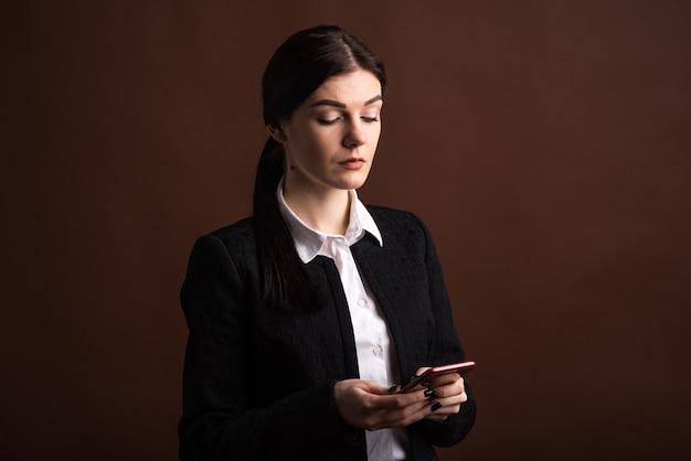 Portret kobiety biznesu, która używa swojego smartfona w studio na brązowym tle
