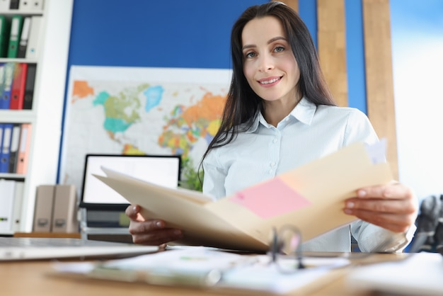 Portret kobiety biznesu siedzącej przy biurku i studiującej dokumenty finansowe