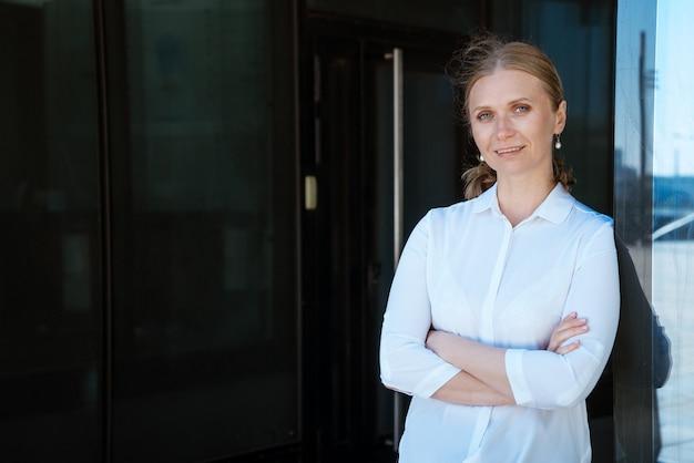 Portret kobiety biznesu w białej koszuli w pobliżu biurowca z założonymi rękami na piersi