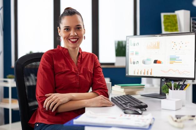 Portret kobiety biznesu w biurze firmy siedzącej przy biurku uśmiechający się do kamery