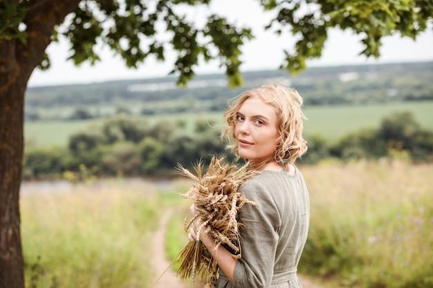 Portret kobiety blondynka ubrana w naturalną lnianą sukienkę z bukietem pszenicy w dłoniach w lecie na świeżym powietrzu.