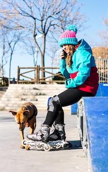 Portret kobiety blondynka w rolkach z psem. siedzą na rampie do jazdy na łyżwach. dzwonię z jej telefonu komórkowego. koncepcja jazdy na łyżwach miejskich.