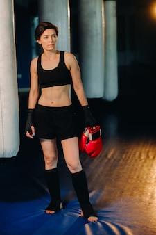 Portret kobiety bokser w czerwonych rękawiczkach na siłowni podczas treningu.