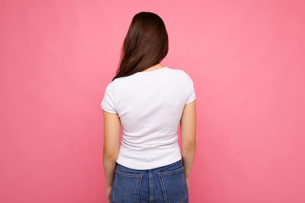 Portret kobiety brunetka w dorywczo biały t-shirt do makiety z tyłu na białym tle na różowym tle z miejsca kopiowania.