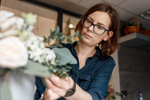 Portret kobiety brunetka w okularach pochylony nad bukietem kwiatów, skoncentrowana praca kwiaciarni.