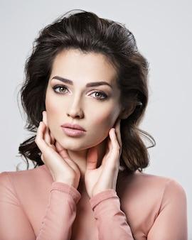 Portret kobiety brunetka z pięknymi długimi brązowymi włosami. dość młoda dziewczyna dorosłych stwarzających w studio. zbliżenie atrakcyjna twarz kobiety.