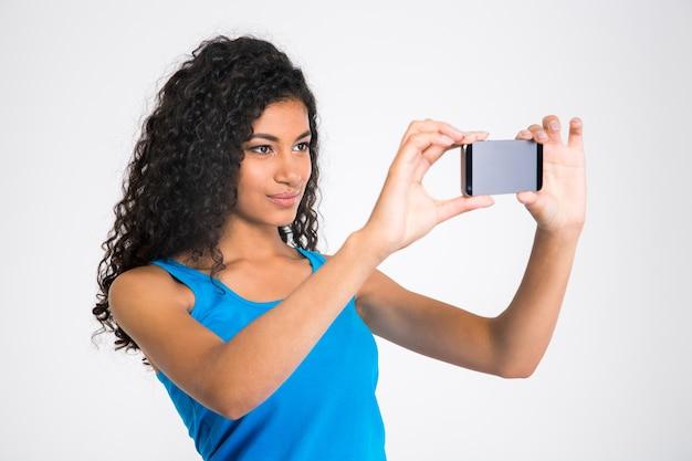 Portret kobiety całkiem afro amerykanki dokonywanie selfie zdjęcie na białym tle na białej ścianie