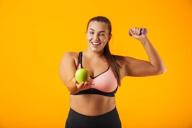 Portret kobiety całkiem nadwagi w sportowy stanik trzyma jabłko i podnoszenia hantle, na białym tle nad żółtym tle