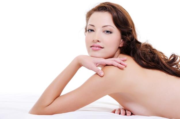 Portret kobiety całkiem rude włosy z nagim ciałem leżącym na białym łóżku