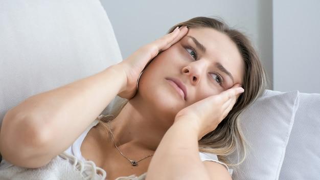 Portret kobiety cierpiącej na ból głowy lub migrenę leżącą na poduszce