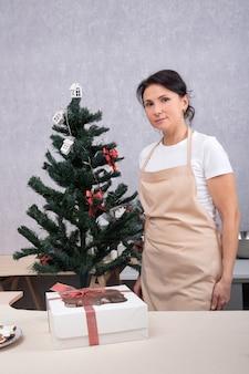 Portret kobiety cukiernik w kuchni obok drzewa nowego roku. rama pionowa.