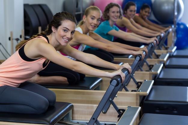 Portret kobiety ćwiczących ćwiczenia rozciągające na reformatorze