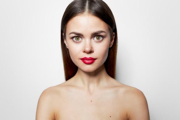 Portret kobiety czerwone usta obnażył ramiona glamour szczegół jasny makijaż tło