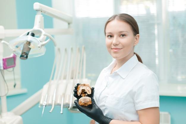 Portret kobiety dentysty w klinice. młoda kobieta lekarz stojący w swoim biurze.