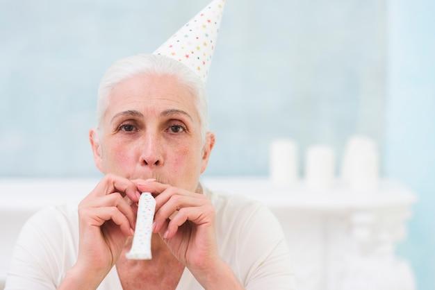 Portret kobiety dmuchania partyjny róg jest ubranym urodzinowego kapelusz