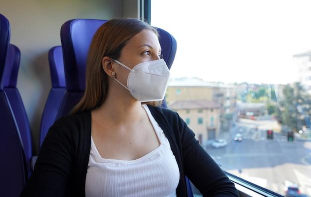 Portret kobiety dojeżdżającej do pracy w masce ochronnej ffp2 kn95 siedzącej w pociągu