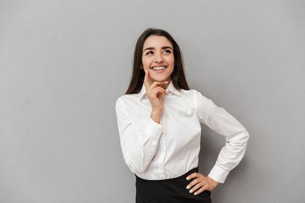 Portret kobiety dwudziestki sukcesu w białej koszuli patrząc na bok i trzymając palec na policzku podczas uśmiechu, odizolowane na szarej ścianie