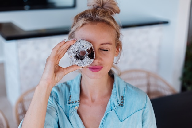 Portret kobiety europejskiej o blond włosach, ciesząc się pączkami w kuchni w domu willi.