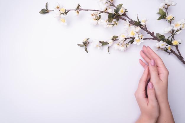 Portret kobiety fashionrt kwitnie w dłoni z jasnym kontrastowym makijażem.