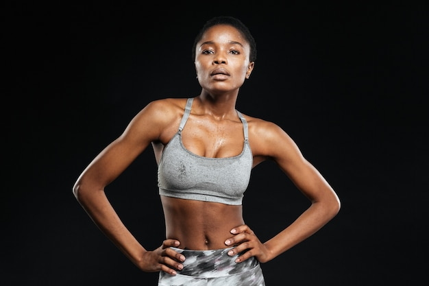Portret kobiety fitness pozuje na białym tle na czarnej ścianie