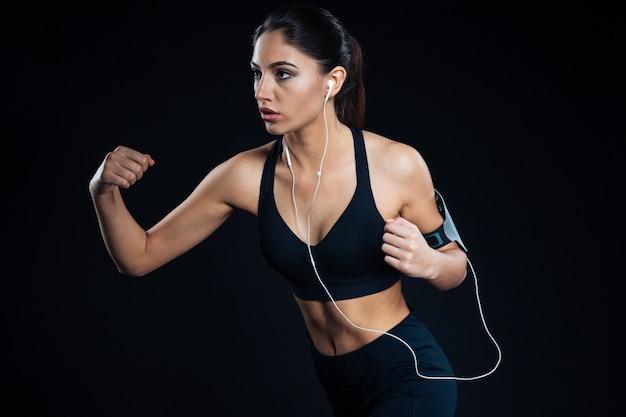 Portret kobiety fitness trenującej ze słuchawkami na czarnym tle