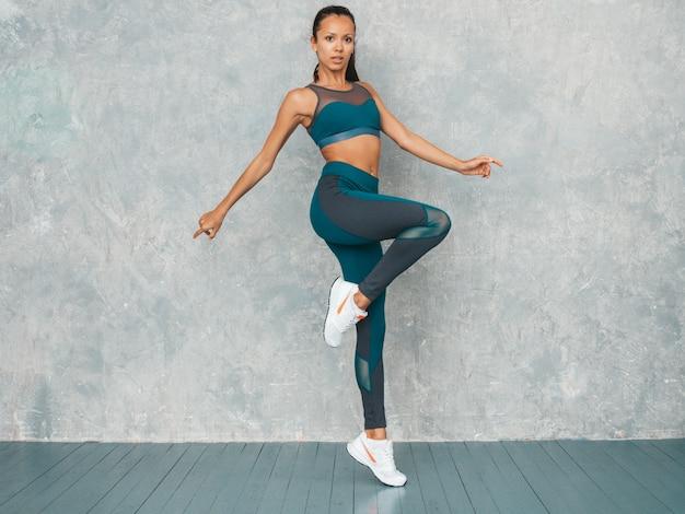 Portret kobiety fitness w odzieży sportowej, patrząc pewnie. młoda kobieta noszenia odzieży sportowej. piękny model z idealnie opalone ciało. skoki kobiet w studio w pobliżu szarej ściany